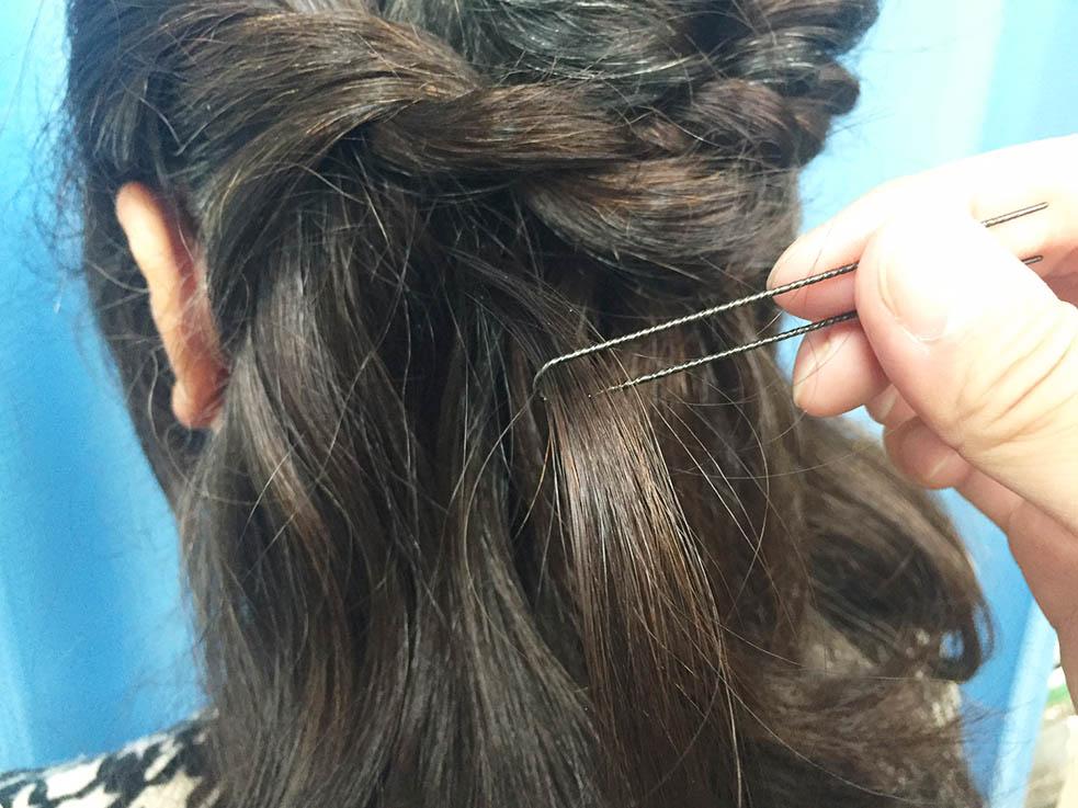 5.くるりんぱの結び目近くの毛束にUピンを通す