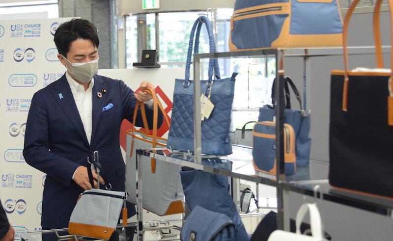 展示会にて漁網由来の鞄を手に取る小泉大臣