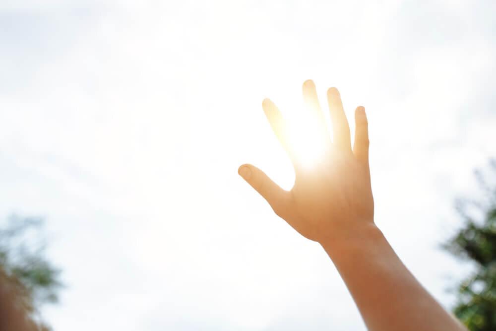 太陽に手を向ける人