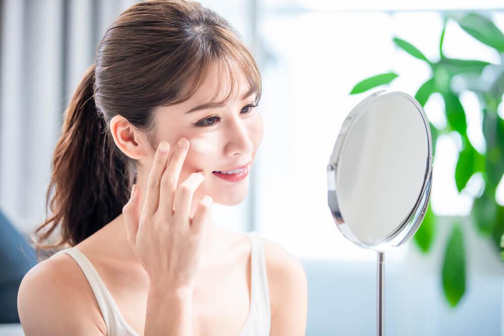 顔に日焼け止めを塗る女性