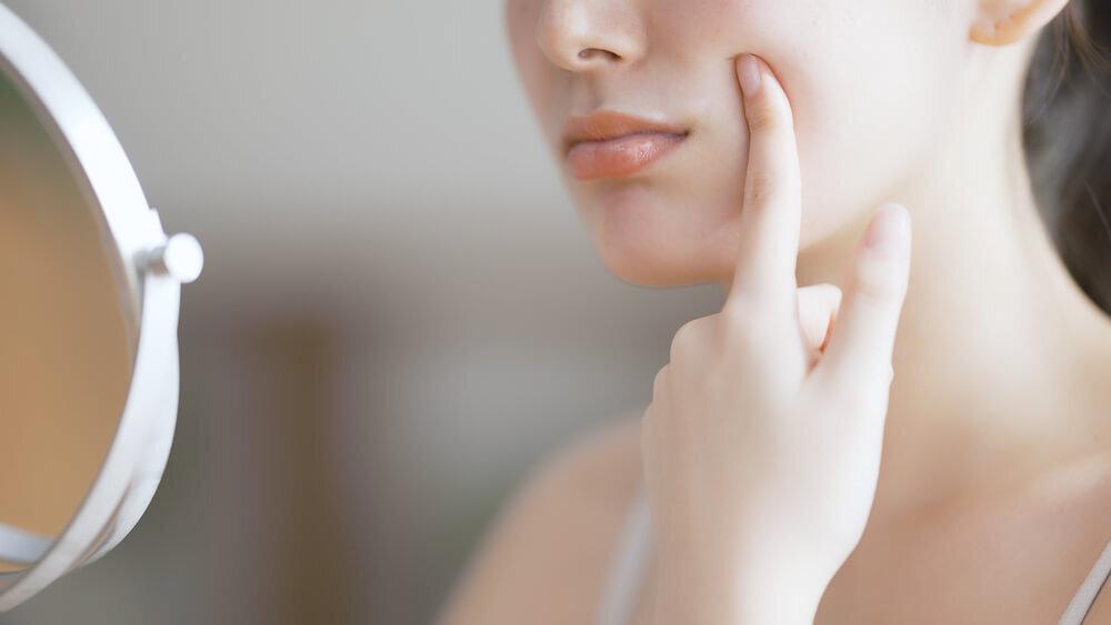 鏡を見てシミをチェックする女性