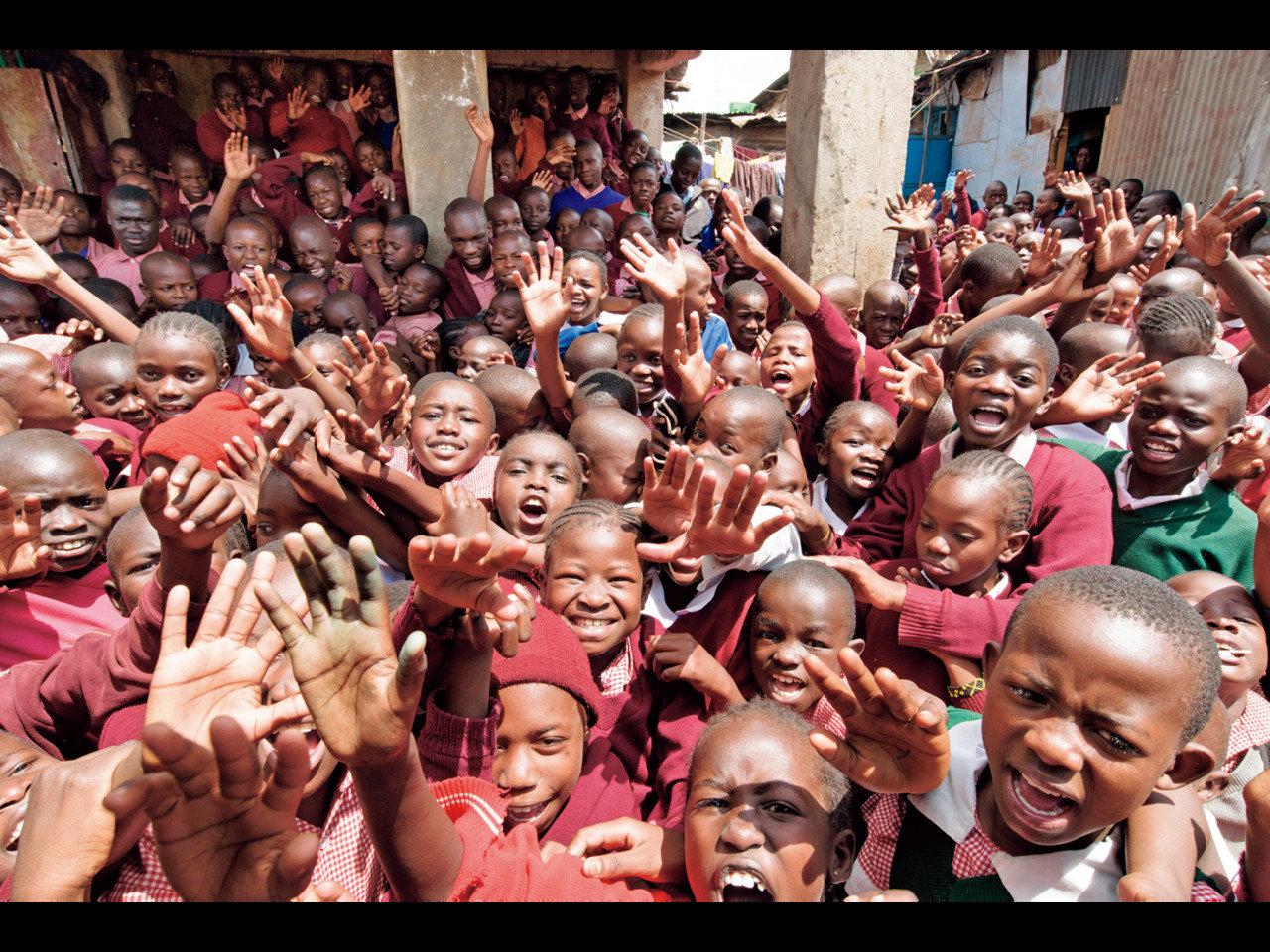 トタン板でつくられた小学校を訪問し、元気な子どもたちにシューズを寄贈しました。