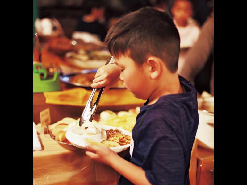 『こども食堂』で、テーブルに並べられた大皿料理から好きな食べ物を自分で皿によそう男の子。リンゴ、好きなんだね!