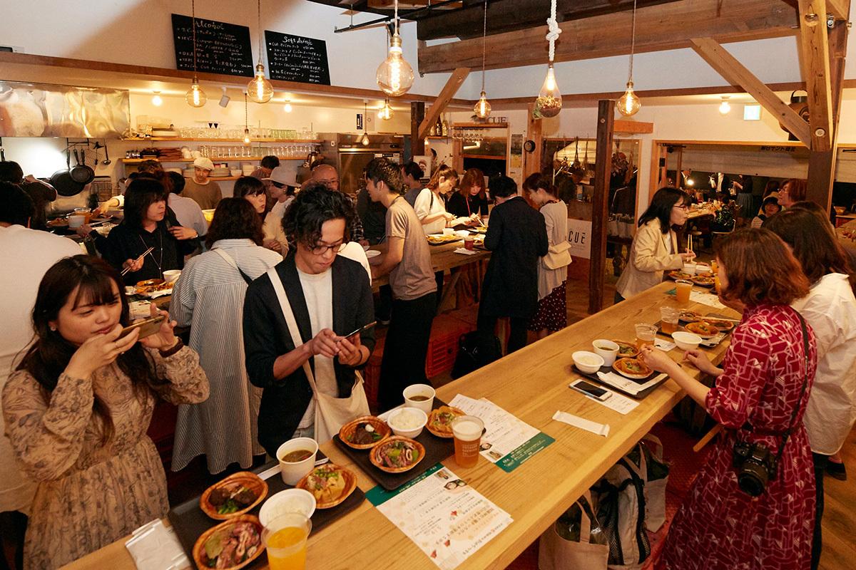 大勢の人で賑わう『the CUE』のカフェバーエリア。積極的に来場者のテーブルに行き会話をする、料理人たちの姿が印象的。
