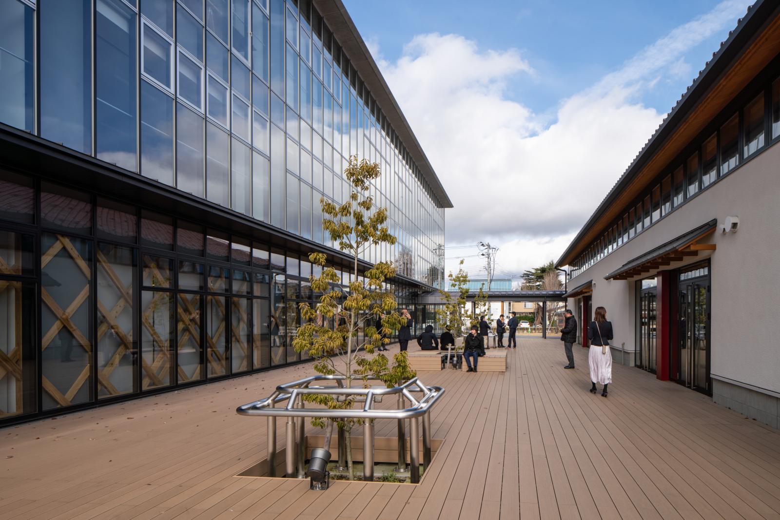 「AiCT」オフィス棟(左)と交流棟(右)はウッドデッキのパブリックスペースでつながる。市民と企業が出合う交流スペースとしての機能もある