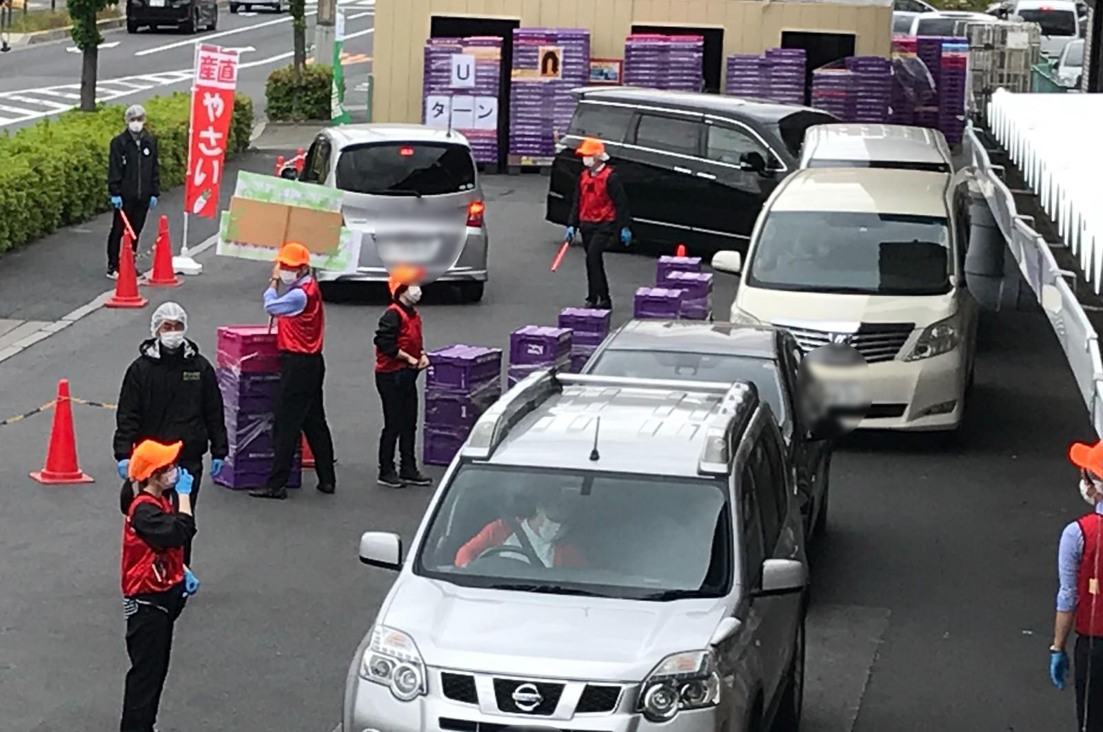 配送センター前にて。購入者たちの車が並ぶ