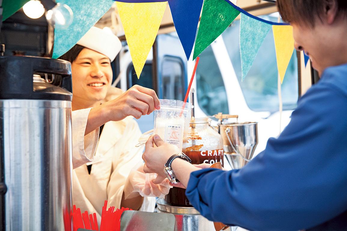 「カワセミ号」でコーラを提供する小林さん。水兵の帽子がトレードマーク。