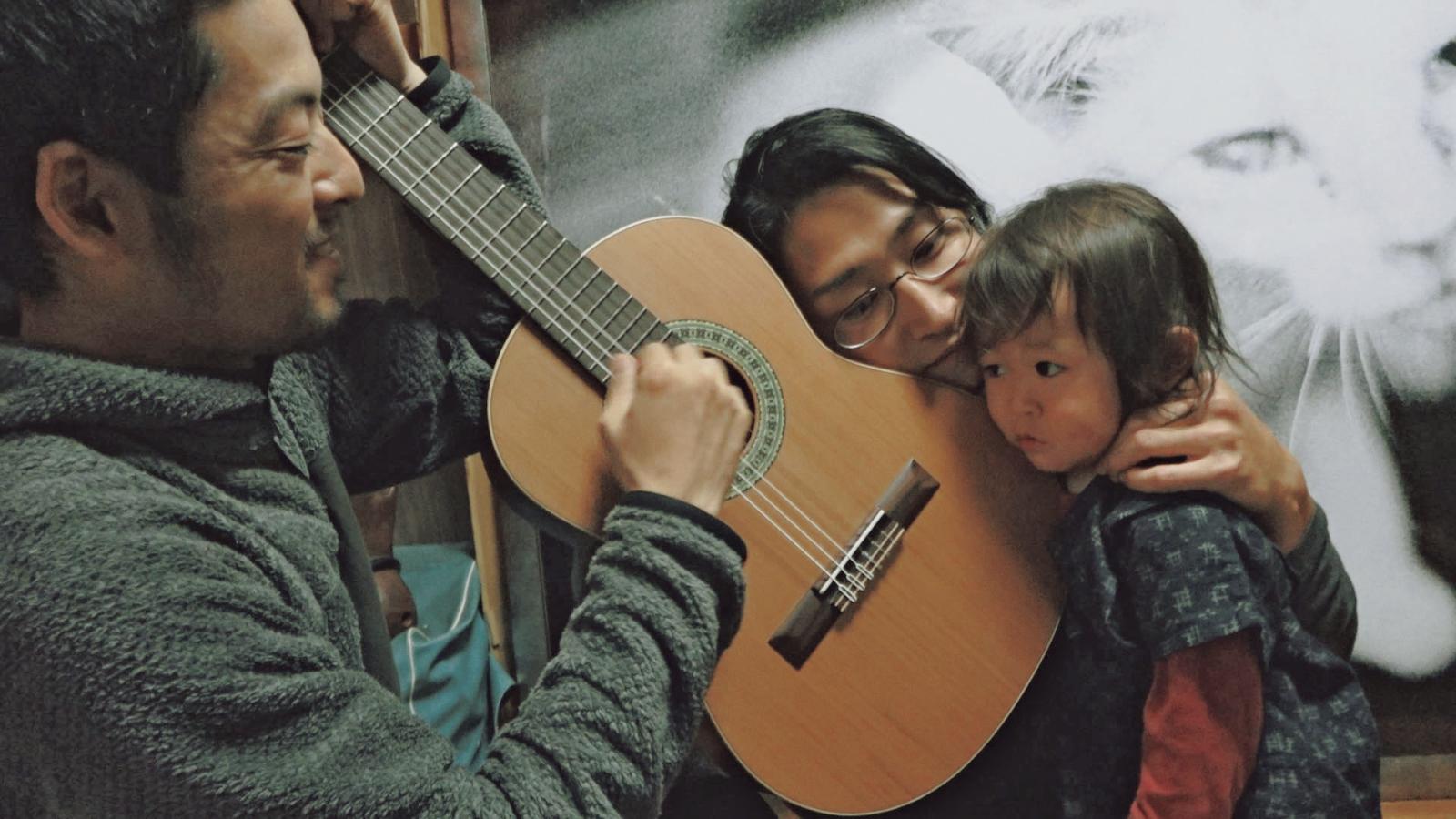 七尾氏のギターの音を聴く齋藤氏と息子の樹(いつき)くん。
