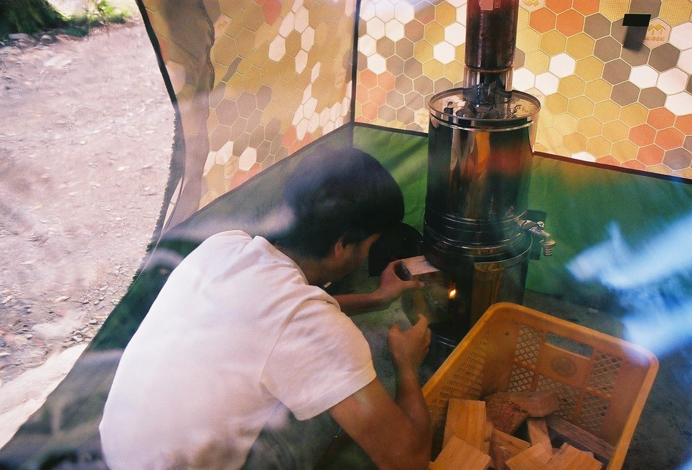 テントの中で薪ストーブをつける斎藤さん