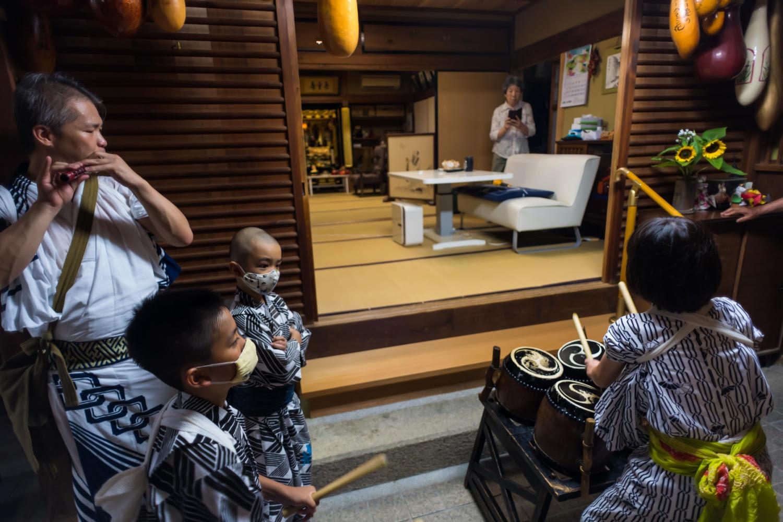 お盆に帰ってきた「お精霊さん」への供養である棚経。宮川さんの笛に合わせて子どもたちがご先祖さまに太鼓を叩く。
