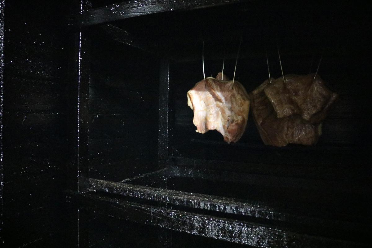 燻煙室で燻されたベーコン
