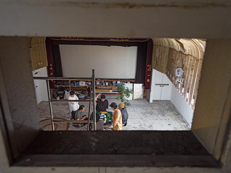 映写室からシアターを見る。このときは、作業の合間にメンバーが麻雀を楽しんでいた。