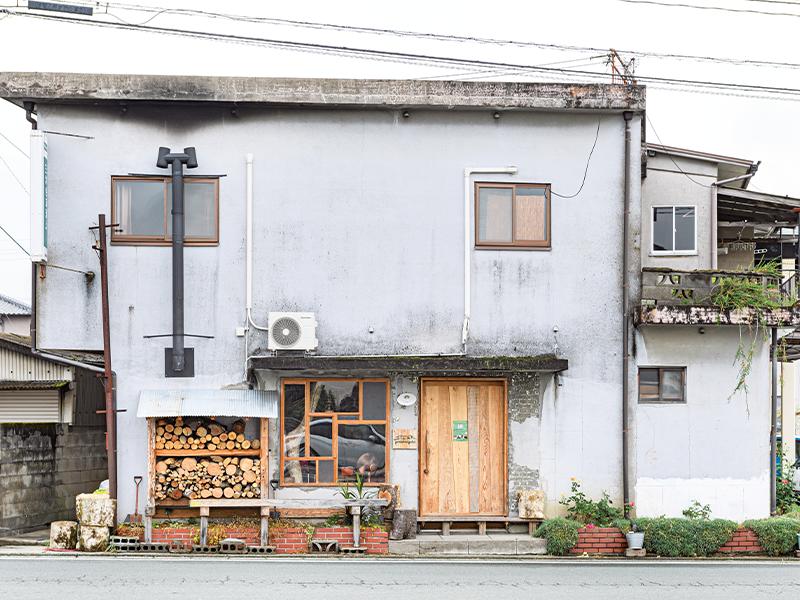 泊まれる山小屋『yamaberinglab』は黒木町の町中にある。入口横に薪が積まれている。