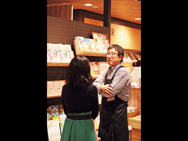 玲音さんの書籍が並ぶ棚の前の田口さん(右)と玲音さん。