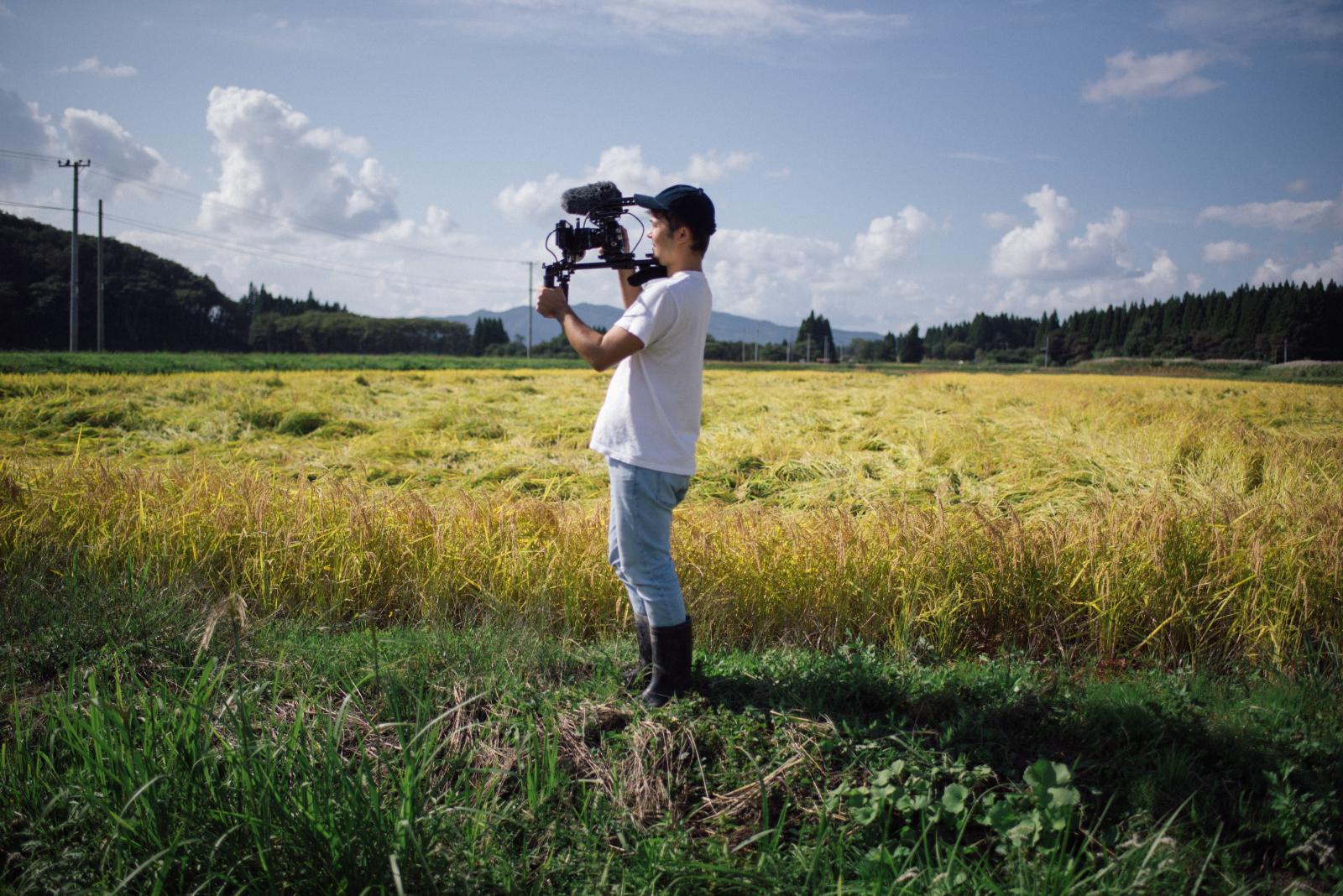 田んぼの中で撮影する栗原さん