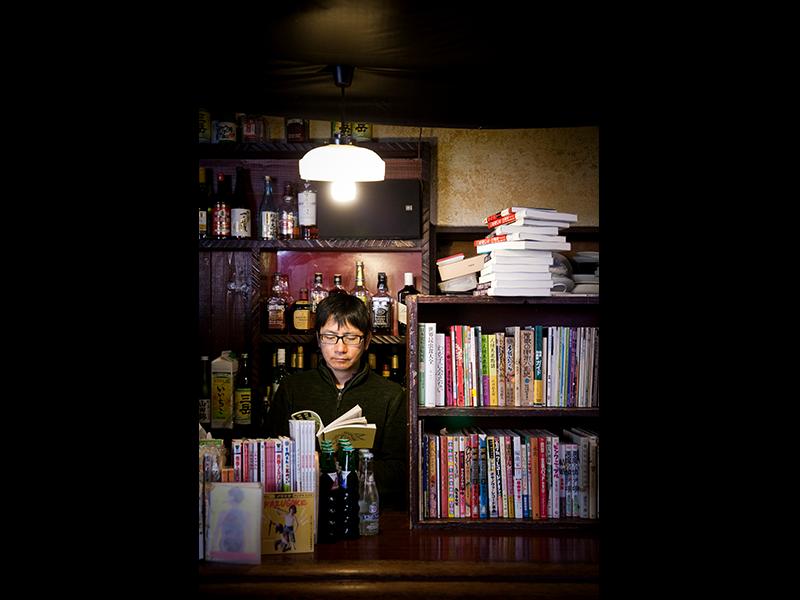 カウンターの中で本を手にする、店主の門田さん。一見、気難しそうだがそんなことはない。古本と中古バイクと相撲が好きな、1967年生まれのナイスミドルだ。