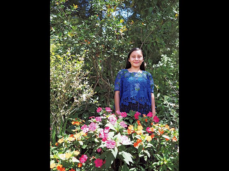 自宅の敷地にある、花でいっぱいの自慢の庭に立つロンディさん。