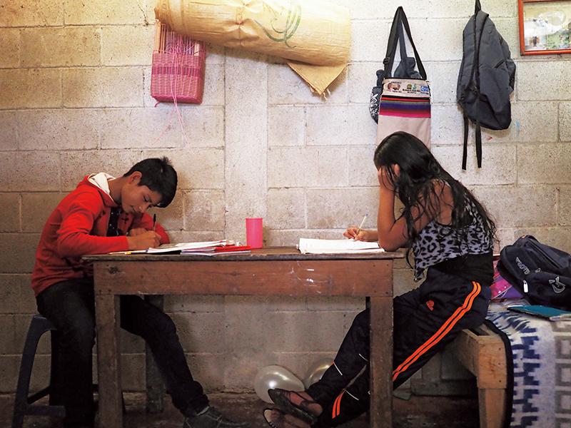 自宅で学校の宿題をこなすロンディさんの弟と妹。
