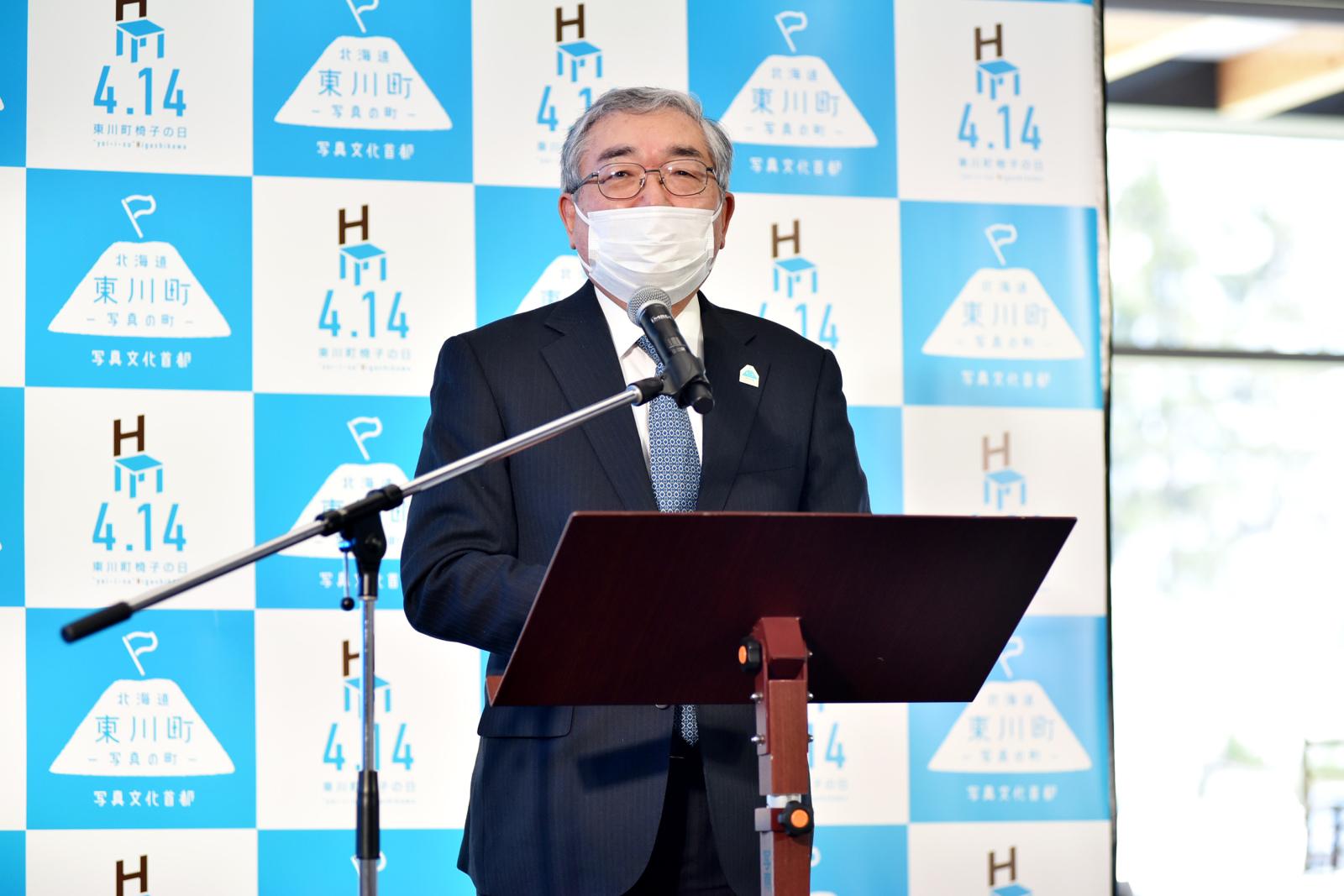 「椅子の日」記念セレモニーのあいさつに立つ東川町町長の松岡市郎さん。
