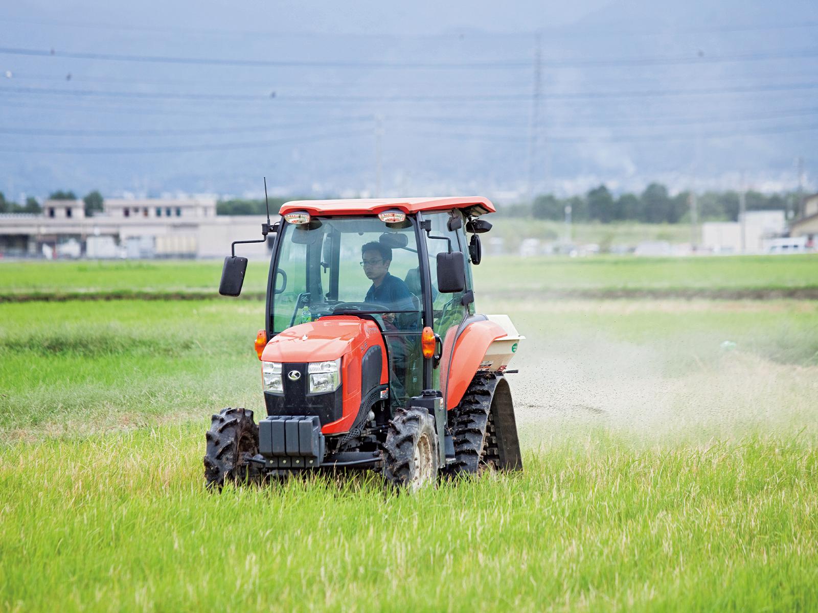 コンバインの後部に肥料を積み、稲刈り後の田んぼを走りながら、来年のために肥料を撒く。