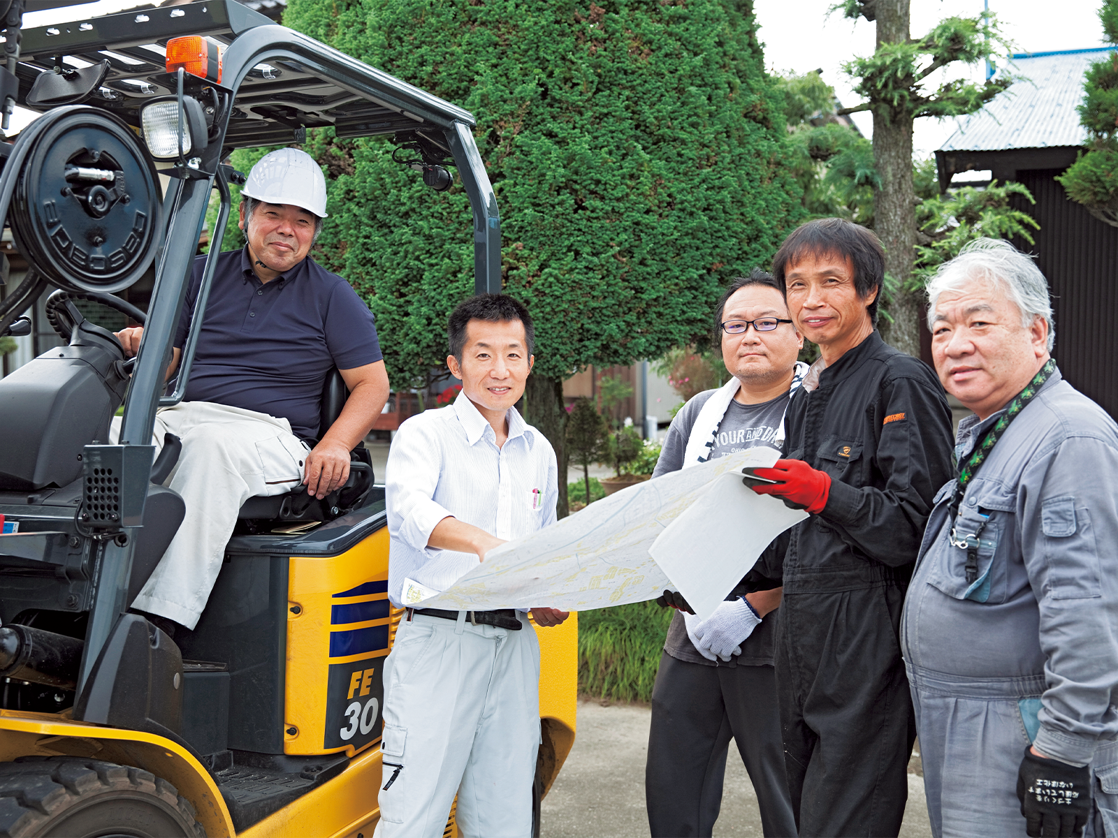 田んぼの持ち主から肥料撒きを請け負っているJA青壮年部と、調整役を務める生活環境課技師の政二さん(左から2人目)。メンバーが肥料撒きを実施。