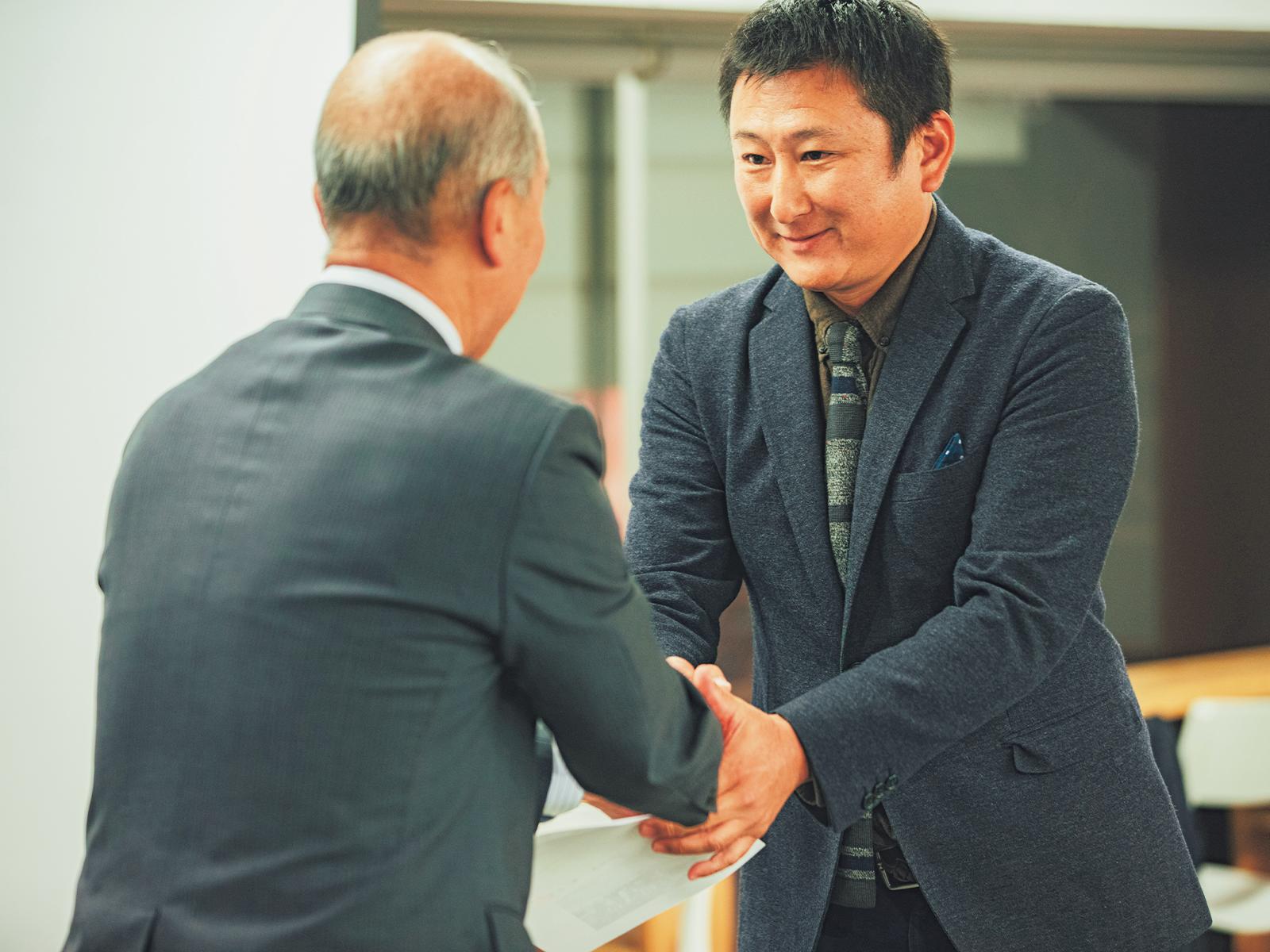 修了証を受け取り、副村長と握手を交わす受講生。