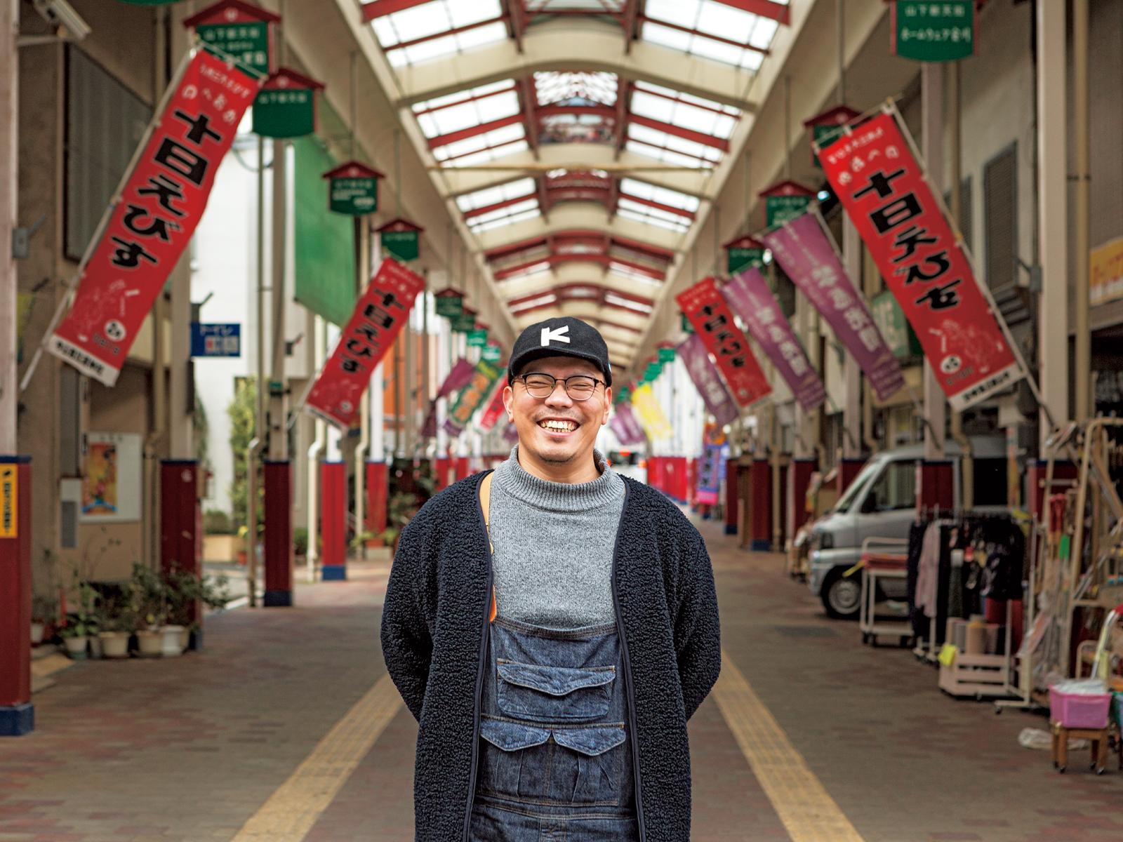 『n計画』近くの商店街に経つ甲斐さん。市外から来た人に見どころ、おもしろさを伝えながら市内を案内することも増えた。