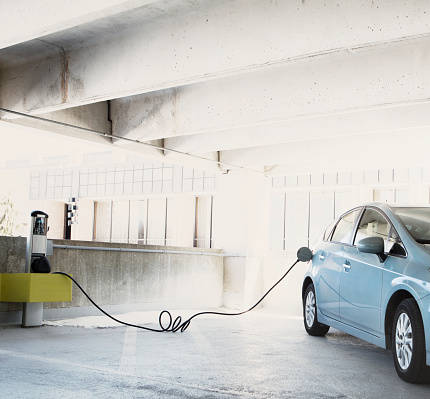 Hybrid car plugged in for e...