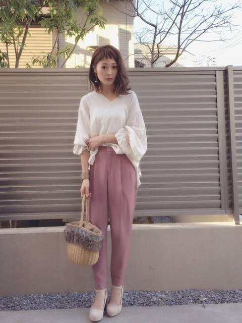 白ブラウスにピンクのジョガーパンツに小物はベージュで女...