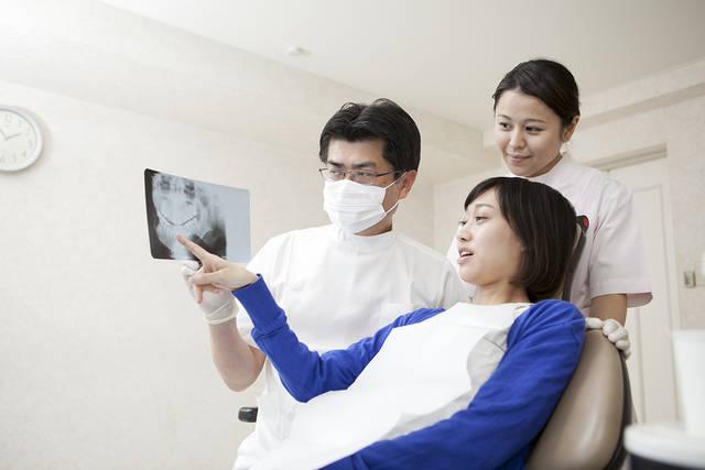 女性患者にレントゲンを説明する歯科医と歯科助手 (m015-254) | 無料人物写真フリー素材の【ビジトリーフォト】商用利用OK (7807)