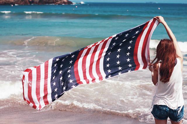 海で旗をたなびかせる少しワイルドな女の子のフリー写真画像|GIRLY DROP (3107)