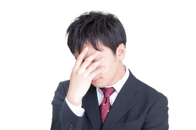 頭を抱えてひどく落ち込む男性|フリー写真素材・無料ダウンロード-ぱくたそ (3387)