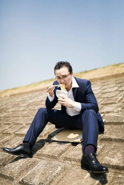 土手で昼食を済ます営業中のビジネスマン|フリー写真素材・無料ダウンロード-ぱくたそ (3391)
