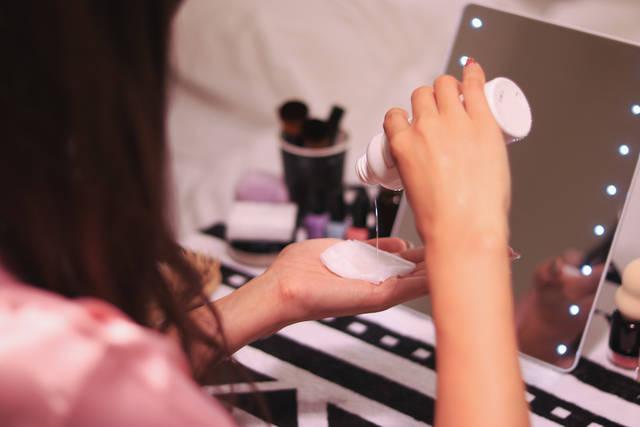 ドレッサーで化粧水をコットンにつけている女の子のフリー写真画像|GIRLY DROP (5044)