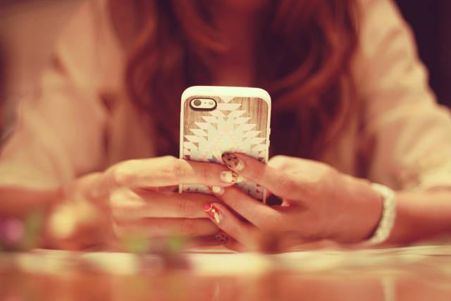 机でスマートフォンを操作する女の子のフリー写真画像|GIRLY DROP (7177)