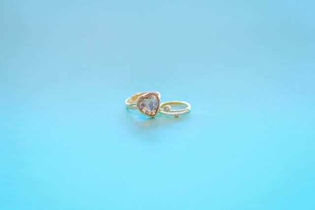 エメラルドグリーンの背景に映えるゴールドの指輪たちのフリー写真画像|GIRLY DROP (9983)