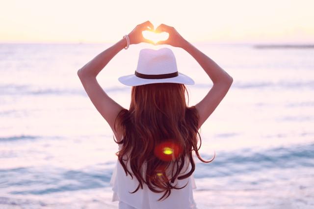 海に落ちていく夕陽にハートの手をかざす女の子のフリー写真画像|GIRLY DROP (10455)