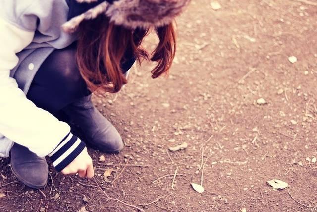 いじけて木の枝で砂に不満を書く女の子のフリー写真画像|GIRLY DROP (10518)