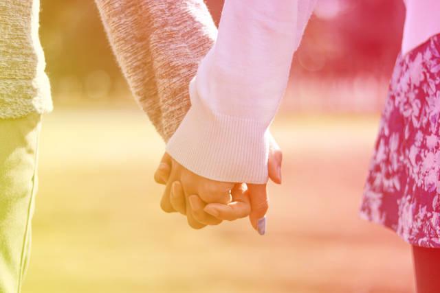 公園で仲良く手をつなぐ付き合いたてのカップル(暖色グラデーション)のフリー写真画像|GIRLY DROP (13639)