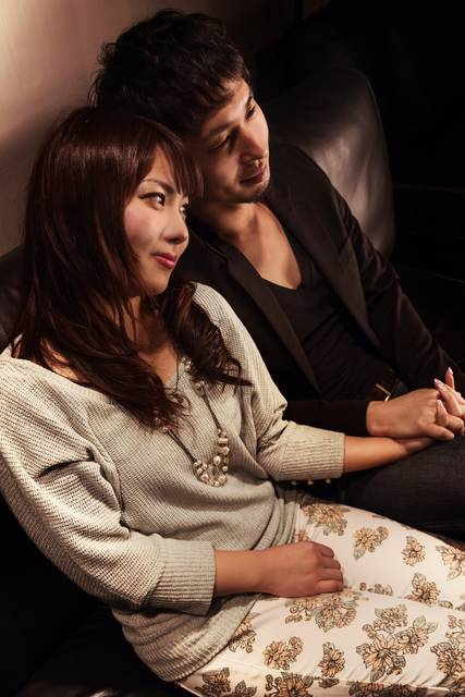ソファーの上で手を握り合う男女|ぱくたそフリー写真素材 (14465)