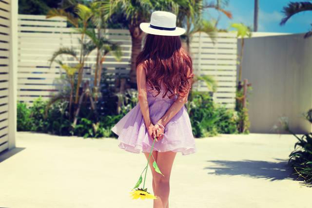後ろ手にひまわりを持って歩いている女の子の画像|おしゃれなフリー写真素材:GIRLY DROP (14468)