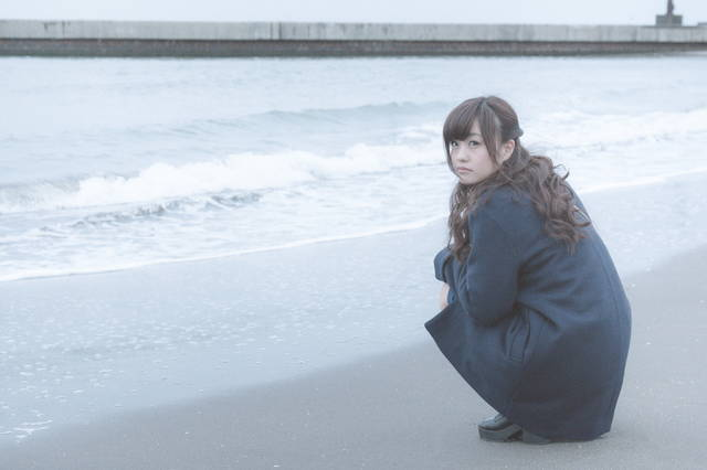 砂浜でいじける女性|ぱくたそフリー写真素材 (16078)