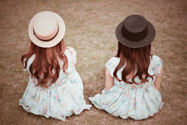 草原に座って景色を見ている双子の女の子たちの画像|おしゃれなフリー写真素材:GIRLY DROP (16369)