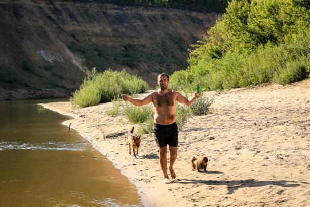 幸せな男は、2匹の犬と一緒に砂浜に沿って、大きな川の土...