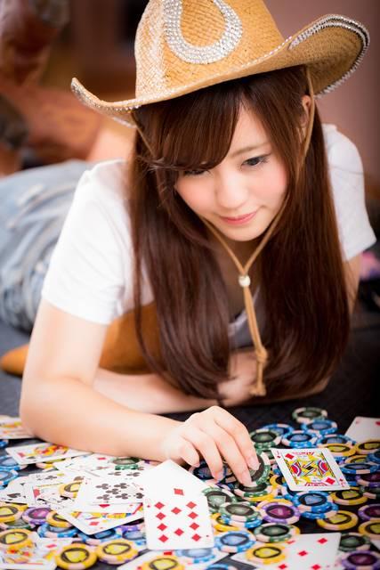 大量のポーカーコインを見て微笑むカウガール|ぱくたそフリー写真素材 (986)