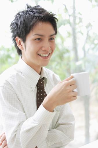 Businessman having coffee break by window in small office