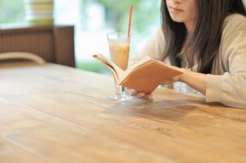 Woman reading a book in a cafe