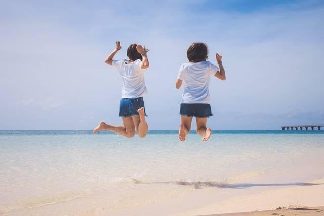 砂浜でジャンプをするいかにもリア充な双子コーデの二人組の画像|おしゃれなフリー写真素材:GIRLY DROP (49113)