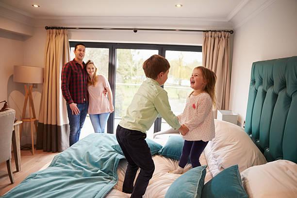 ご家族でのバケーションに、ホテルのベッドで遊ぶお子様