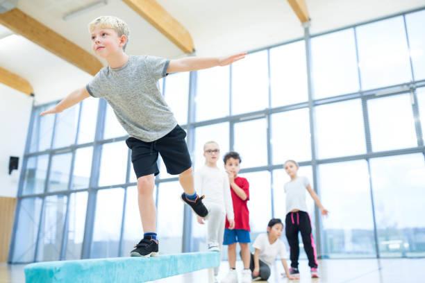 Schoolboy balancing on bala...